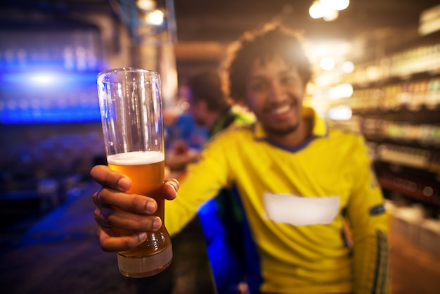 Il tifoso di calcio sta sollevando il suo bicchiere di birra mentre celebra seduto al bar del pub.