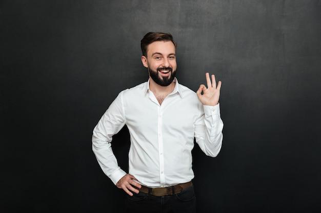 Il tipo adulto in ufficio che posa sulla macchina fotografica, che sorride e che gesturing con il segno giusto che esprime tutto va bene sopra grigio scuro