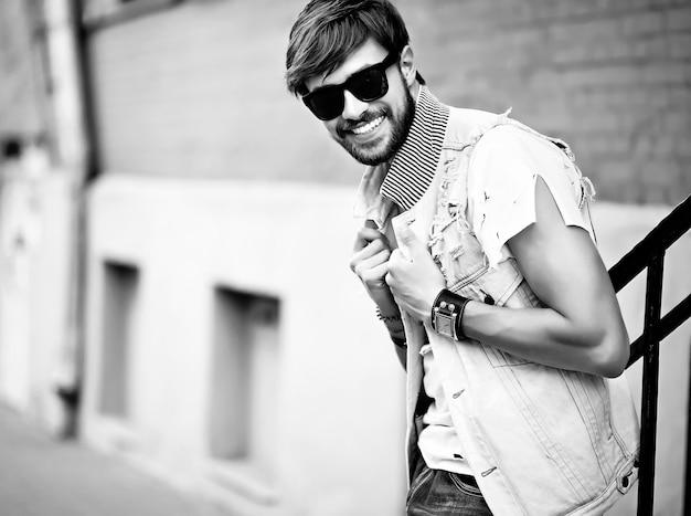 Il tipo bello sorridente dell'uomo divertente dei pantaloni a vita bassa in estate alla moda copre la posa nella via