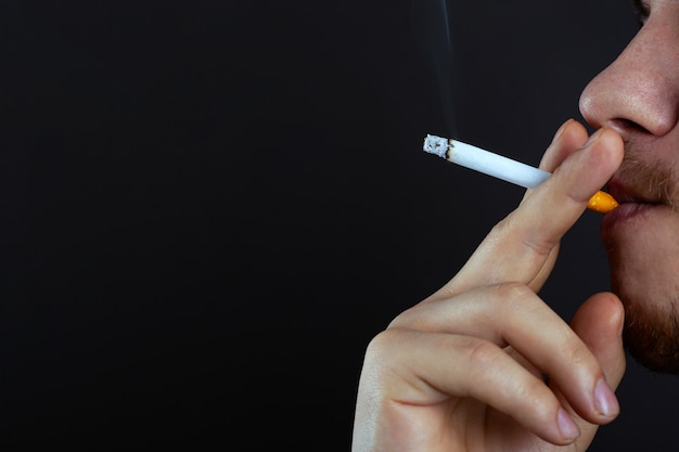 Il tipo che tiene una sigaretta bruciante respira il fumo che fuma il danno dal primo piano dello spazio della copia della nicotina.