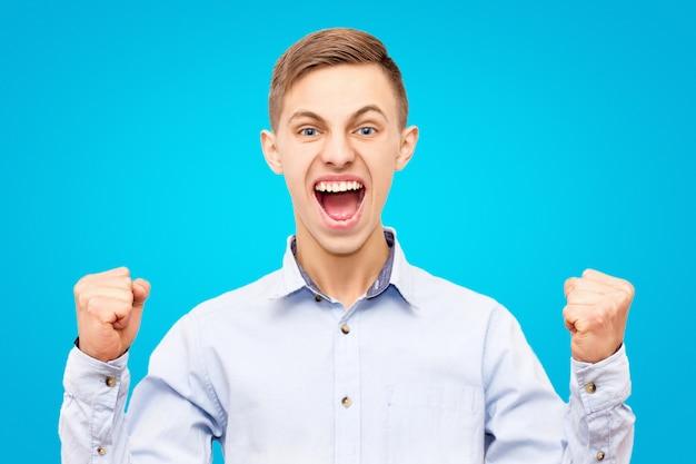Il tipo in camicia blu si rallegra la vittoria isolata su fondo blu, mani sollevate su