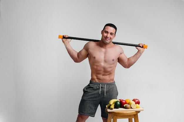 Il tipo sexy sportivo sta con una barra del corpo su un fondo bianco. fitness, alimentazione sana