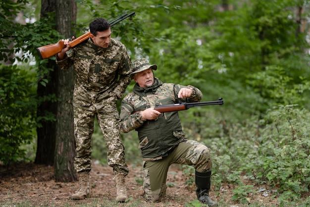 Il tiratore ricarica il fucile da caccia papà e figlio a caccia.