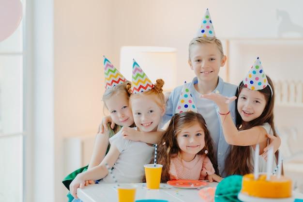 Il tiro al coperto di bambini felici celebra la festa con i coriandoli che cadono, indossa cappelli da festa a cono, posa vicino al tavolo festivo con torte