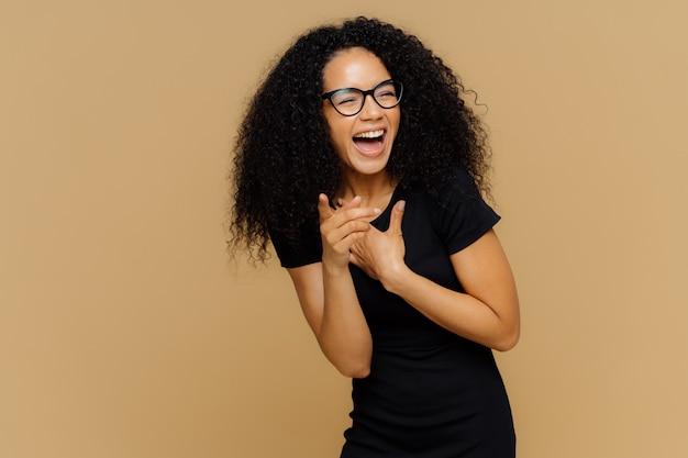 Il tiro al coperto di una felicissima femmina ride ad alta voce, nota una scena divertente, indica la telecamera