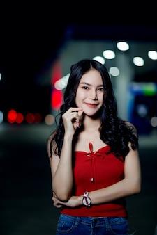 Il tiro di foto della bella ragazza come nel vestito rosso alla notte