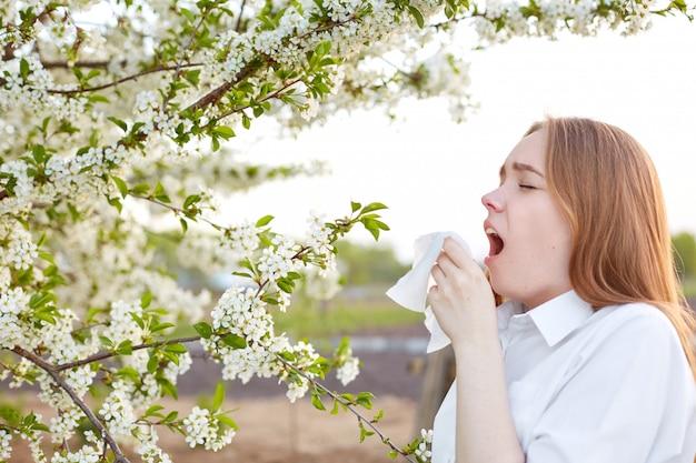 Il tiro orizzontale di una giovane donna malata starnutisce nel fazzoletto, vestito con una camicia elegante, ha un'allergia al fiore, vestito con una camicia elegante