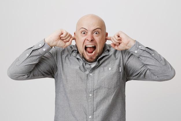 Il tizio calvo infastidito arrabbiato chiudeva le orecchie con le dita, imprecando contro i vicini rumorosi, gridando