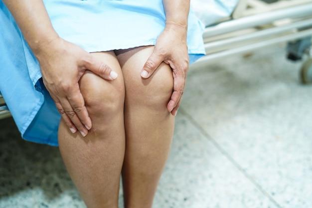 Il tocco e la sensibilità pazienti asiatici della donna di mezza età dolore il suo ginocchio: concetto medico sano.