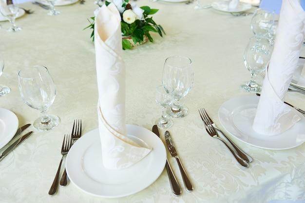Il tovagliolo ben piegato sui piatti, serve un banchetto celebrativo