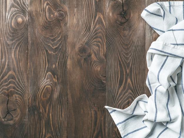 Il tovagliolo di tela sulla tavola di legno, la vista superiore, deride su