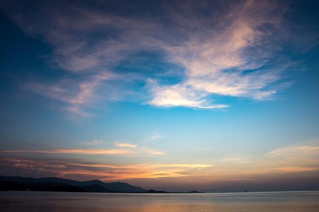 Il tramonto e la luce dorata sulla superficie del mare, bella alba nuvolosa al paesaggio del mare