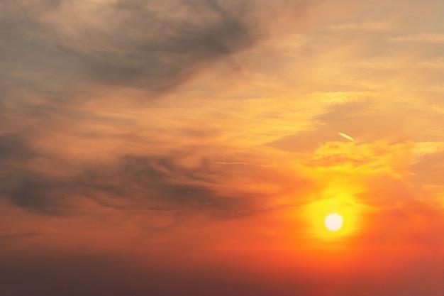 Il tramonto nel cielo è rosso-arancio e nuvole grigie sotto forma di macchie su cui splende il sole.