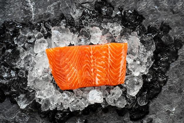 Il trancio di pesce di color salmone crudo su ghiaccio sopra fondo di pietra scuro.