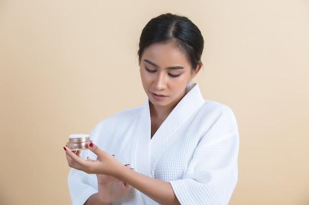 Il trattamento di bellezza con la donna tiene in mano una crema idratante