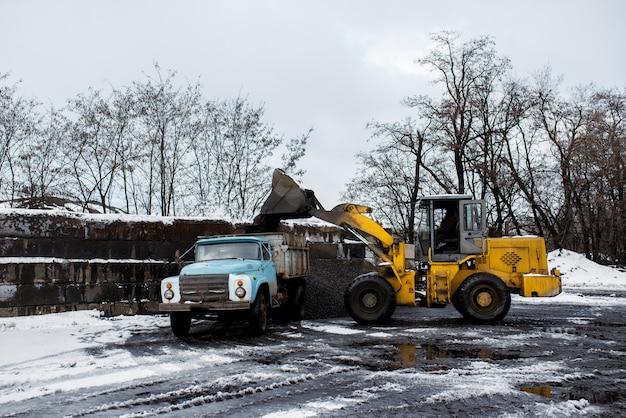 Il trattore carica carbone nel camion.