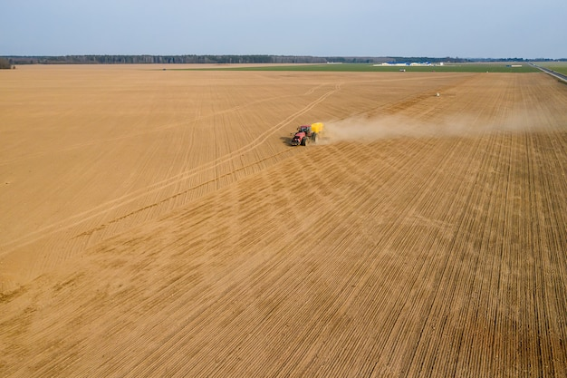Il trattore semina grano nella vista superiore del campo