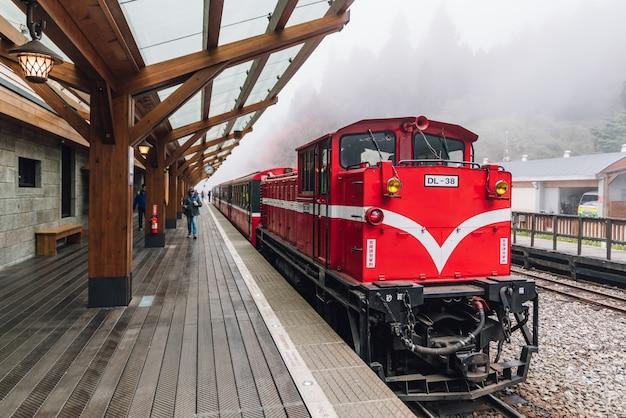 Il treno rosso su alishan forest railway si ferma sulla piattaforma della stazione ferroviaria di zhaoping a alishan, taiwan.