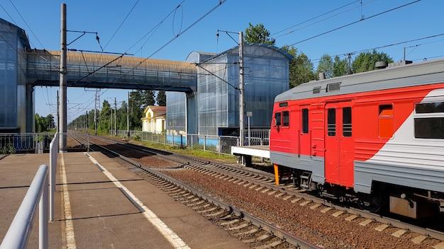 Il treno suburbano arriva alla stazione di estate il giorno soleggiato. piattaforma ferroviaria con treno lungo il percorso.