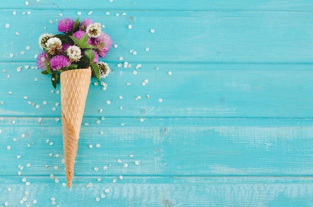 Il trifoglio fiorisce in cono per il gelato su fondo blu. vista dall'alto.
