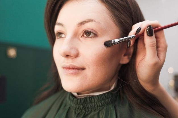 Il truccatore applica la polvere sulla pelle del cliente con un pennello per il trucco. processo di trucco in un salone di bellezza