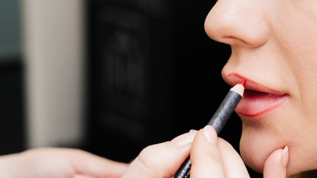 Il truccatore dipinge le labbra con una matita per labbra per una donna in un salone di bellezza