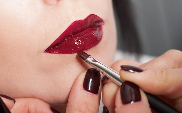 Il truccatore dipinge le labbra di una ragazza con rossetto rosso