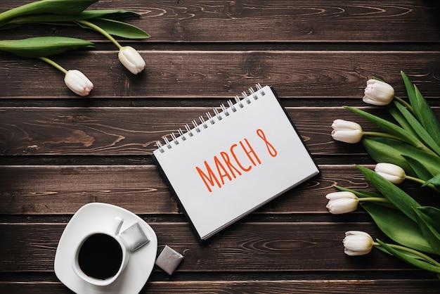 Il tulipano bianco fiorisce con una tazza di caffè su una tavola di legno.