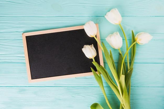 Il tulipano fiorisce con la lavagna in bianco sulla tavola di legno