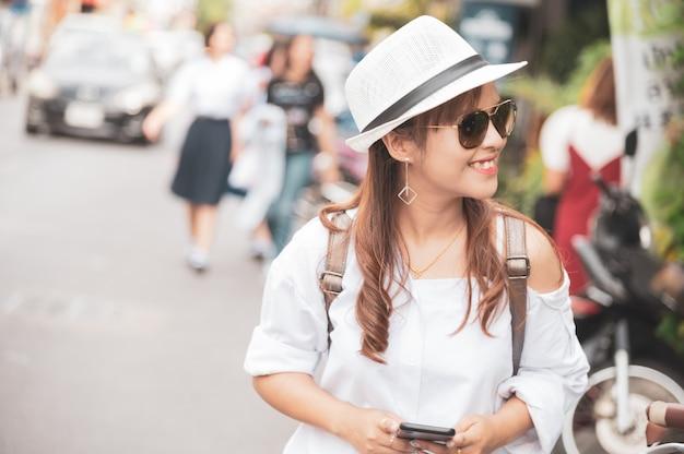 Il turista asiatico della donna sta controllando lo smartphone mandante un sms sulla via, facendo uso dell'app del telefono cellulare per controllare la mappa online.