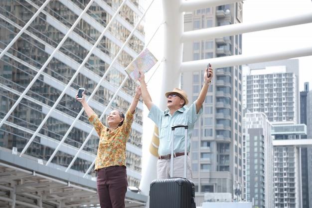 Il turista asiatico sta tenendo la mappa e il telefono cellulare che sollevano la mano su nella città.