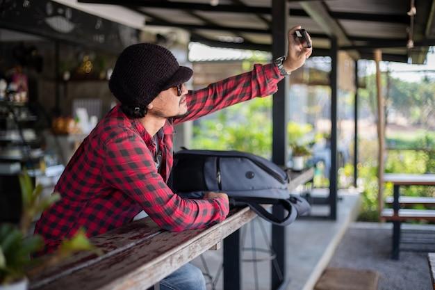 Il turista asiatico sta usando un telefono cellulare per scattare un selfie da condividere sui social media, tramite i social network.