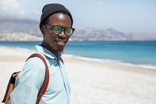 Il turista attraente alla moda dell'uomo di colore si è vestito in abbigliamento e accessori d'avanguardia che posano contro l'acqua blu e la sabbia bianca