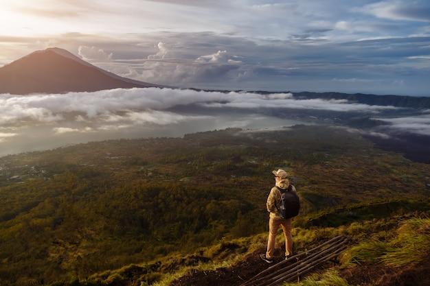 Il turista dell'uomo esamina l'alba sul vulcano batur sull'isola di blai in indonesia. uomo della viandante con il viaggio dello zaino sul vulcano superiore, concetto di viaggio