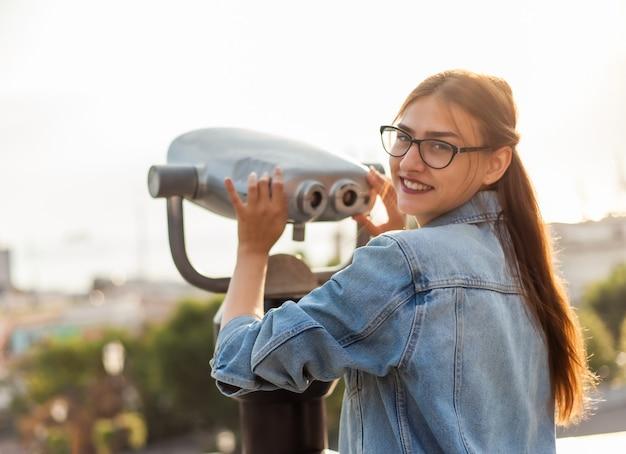 Il turista della giovane donna in una giacca e negli occhiali del denim osserva nel binocolo della città nella città. concetto di viaggio