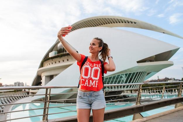 Il turista femminile felice sta prendendo un selfie nella città delle arti e delle scienze a valencia