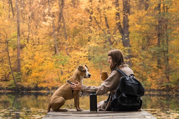 Il turista femminile si siede con il cane vicino al lago e gode della tazza di caffè bevente della bella vista di autunno
