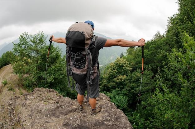 Il turista maschio con lo zaino sta sulla collina