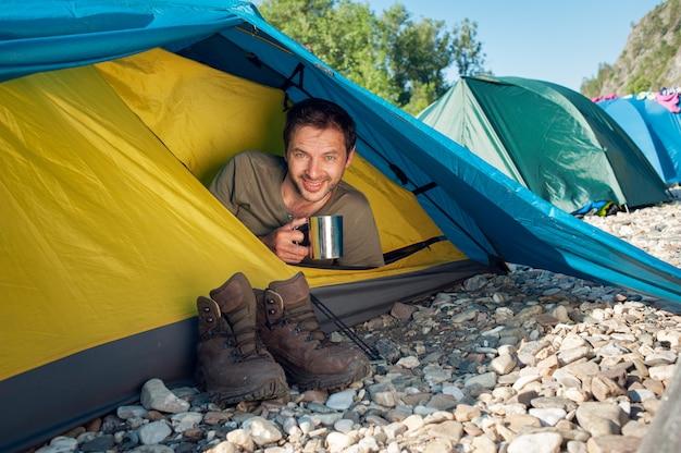 Il turista maschio incontra il buongiorno soleggiato, seduto in tenda turistica con una tazza di tè caldo. immagine di concetto di vacanza attiva.