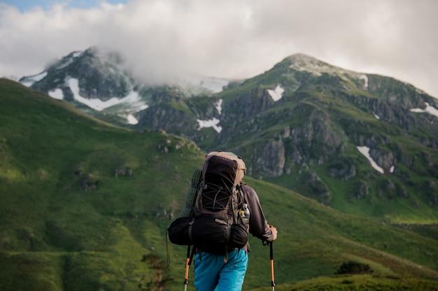 Il turista maschio sta davanti alle montagne