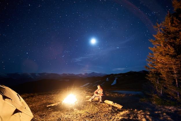 Il turista si riposa nel suo accampamento di notte vicino al fuoco