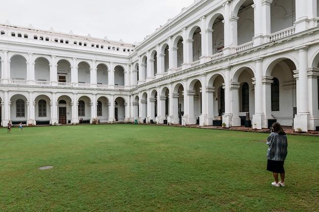 Il turista sta scattando una foto di stile architettonico vittoriano con cortile centrale all'interno del museo indiano