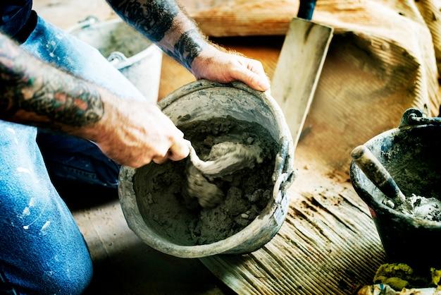 Il tuttofare prepara l'uso del cemento per costruzione
