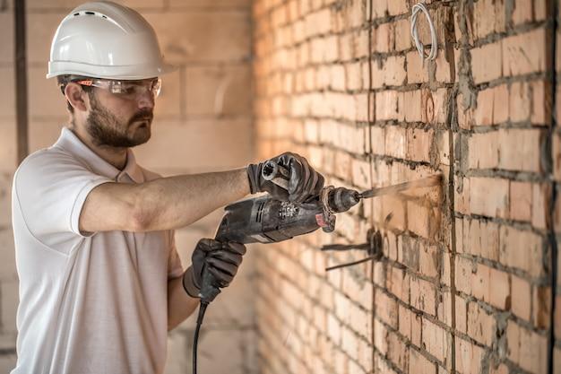 Il tuttofare usa il martello pneumatico, per installazione, operaio professionale nel cantiere. l'elettricista e tuttofare.