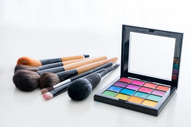 Il vario compone la spazzola con i prodotti di trucco e le estetiche di correttori sulla tavola nel fondo bianco.