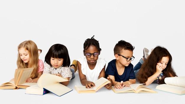 Il vario gruppo di bambini studia il libro colto
