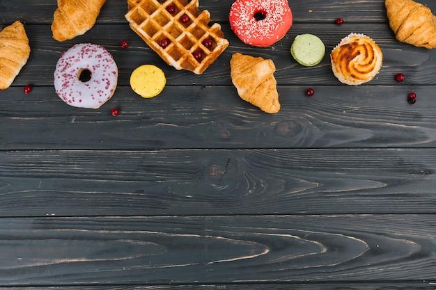 Il vario tipo di dolci ha cotto gli oggetti sulla tavola di legno