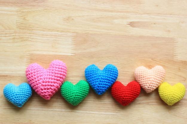 Il variopinto di fatto a mano lavora all'uncinetto il cuore sulla tavola di legno per il giorno di biglietti di s. valentino con copyspace