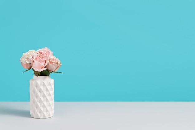 Il vaso ceramico bianco moderno con le rose rosa su fondo blu sta su yable grigio. composizione minimalista con spazio vuoto per il design. concetto di negozio di fiori. biglietto d'auguri