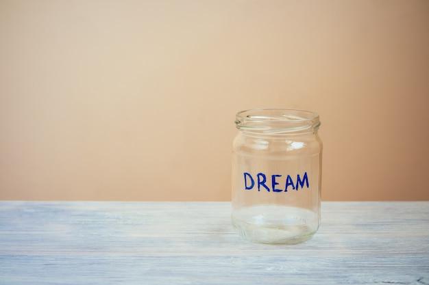 Il vaso di vetro vuoto con un sogno dell'iscrizione è su una tavola di legno blu su un fondo beige